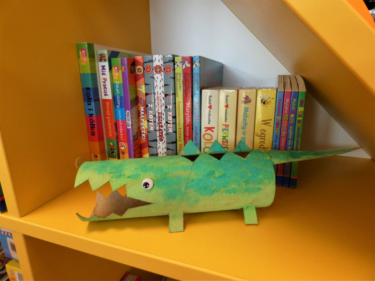 krokodyl wycięty z kartonu pomalowany na zielono, na regale z książkami