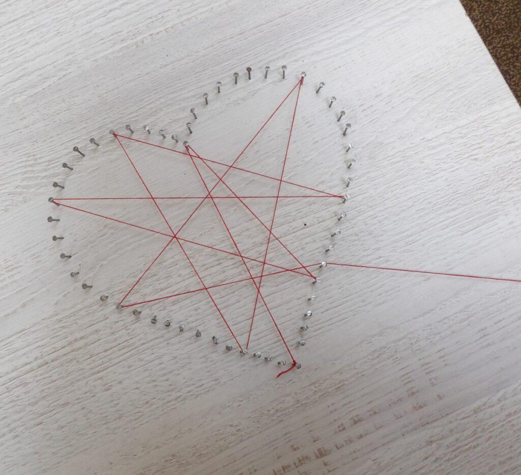 Serce wykonane z powbijanych w deskę gwoździ, o które owinięty jest czerwony sznurek