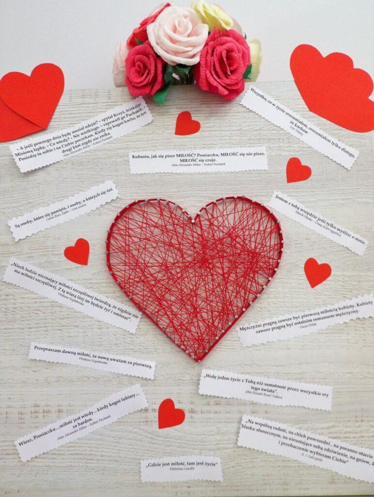 Serce wykonane z powbijanych w deskę gwoździ, o które owinięty jest czerwony sznurek, na desce nalepione karteczki z cytatami oraz papierowe czerwone serduszka
