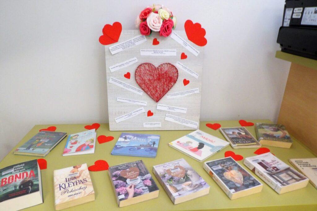 Serce wykonane z powbijanych w deskę gwoździ, o które owinięty jest czerwony sznurek, na desce nalepione karteczki z cytatami oraz papierowe czerwone serduszka, całość położona na stole z książkami