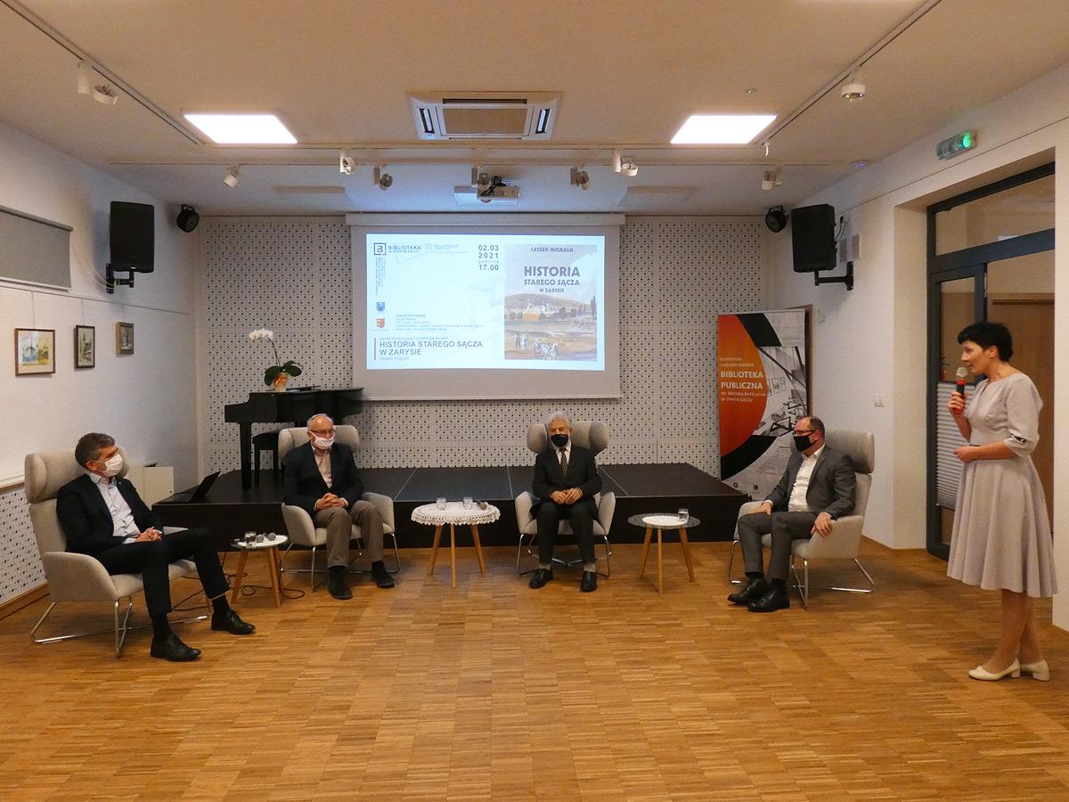 4 osoby siedzące na krzesłach, w tle plakat promocji książki: Historia Starego Sącza w zarysie