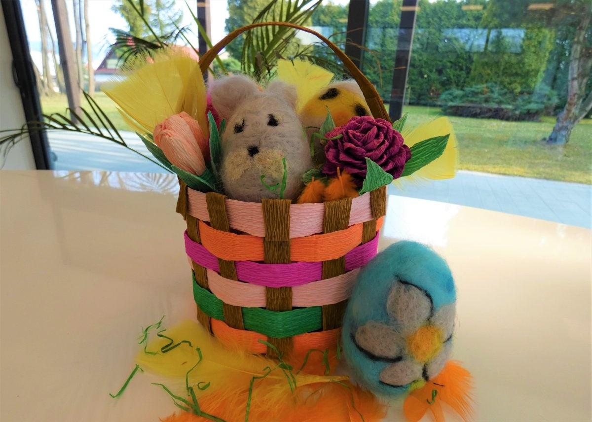 Koszyczek z kolorowej krepiny, w środku pluszowe jajka wielkanocne