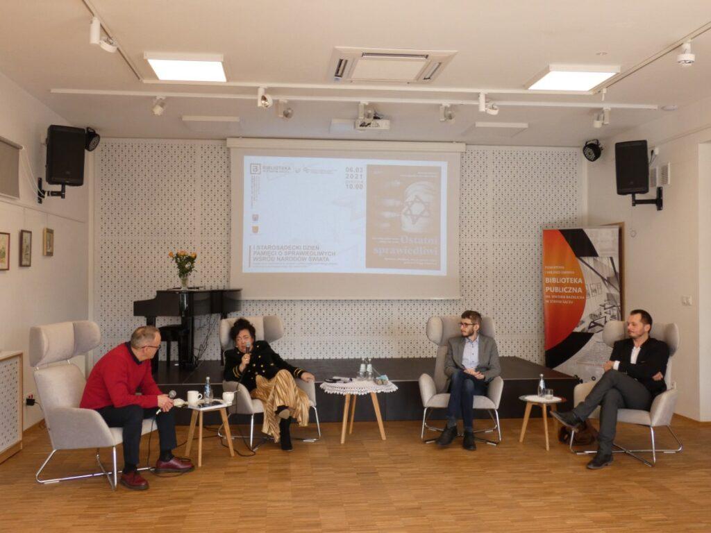 Na zdjęciu pięć osób na sali: cztery osoby siedzą i rozmawiają