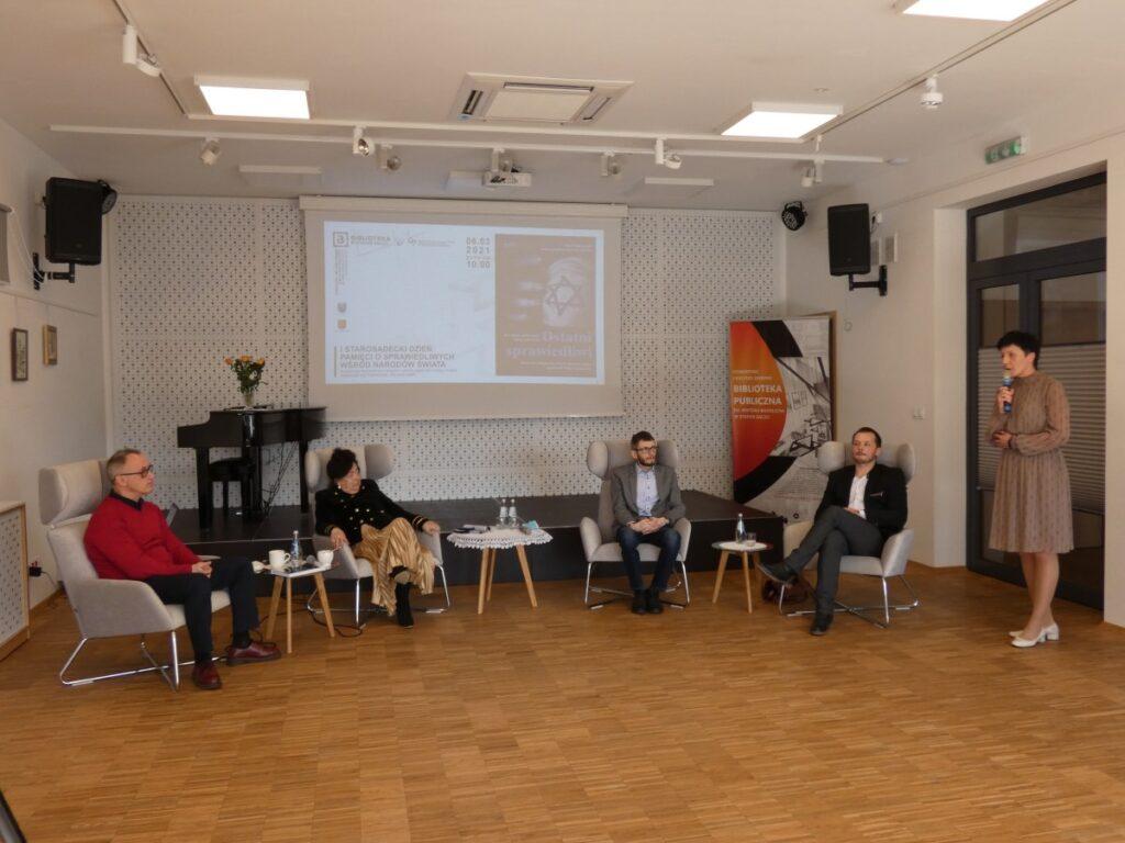 Na zdjęciu pięć osób na sali: cztery osoby siedzą jedna przemawia